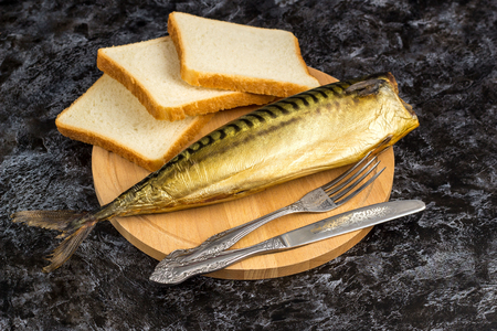One smoked mackerel without head with fork knife cutting board bread on black background