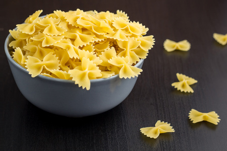 black background with italian raw farfalle or pasta in grey bowl with copy space