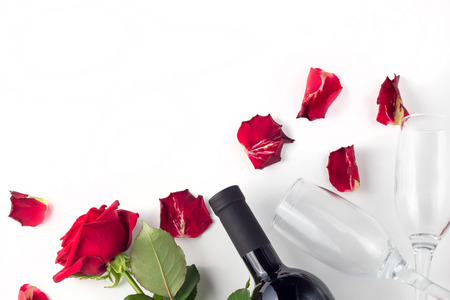 Bottle of wine, glass and red rose with petals on a white background isolated 版權商用圖片