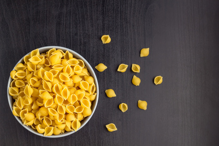 Top view of black background with italian raw conchiglie paste shells in grey bowl with copy space