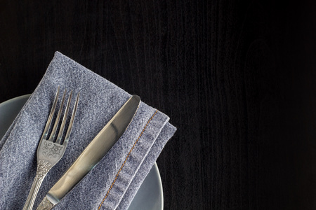 table setting with empty plate napkin fork and knife on black wooden background