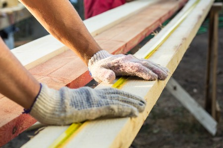 Close up view of a man hands measuring wooden plank with a tape line. Measurement. Building and maintenance.