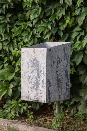 Grey Trash can in park on green leaves background Standard-Bild - 129166491