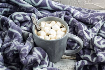 cup of coffee or cocoa with marshmallows and warm plaid on white wooden table. Christmas Winter concept.