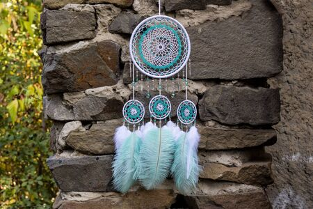 Dream catcher with feathers threads and beads rope hanging. Dreamcatcher handmade Stock Photo - 130952929
