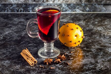 Glass of delicious mulled wine with oranges anise cinnamon on dark table with copyspace Stock Photo