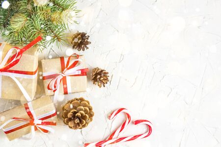 Christmas or New Year decorations background with pine cones, fir branches, gift boxes, and candy canes. Toned bokeh and snow Imagens