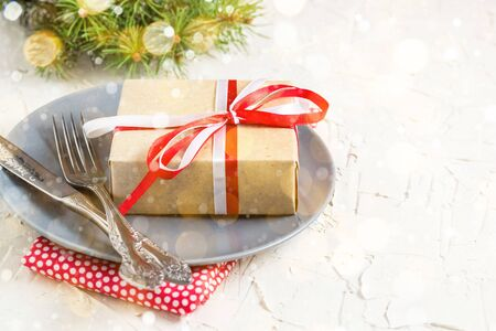 Christmas table setting with gift on plate on white table. Xmas concept top view. Toned bokeh and snow