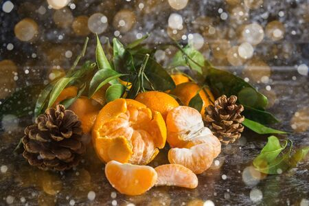 Many orange tangerines with green leaves on dark background. Peeled mandarin slices and cones. Toned bokeh and snow