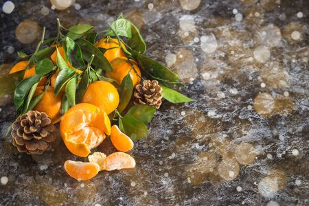 Many orange tangerines with green leaves on dark background with copy space. Peeled mandarin slices and cones. Toned bokeh and snow