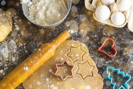 Cooking Christmas gingerbread cookies with ingredients on a dark background. Toned bokeh and snow