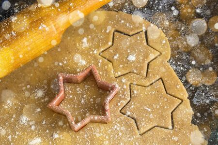 Cooking Christmas gingerbread cookies with rolling pin on a dark background. Toned bokeh and snow