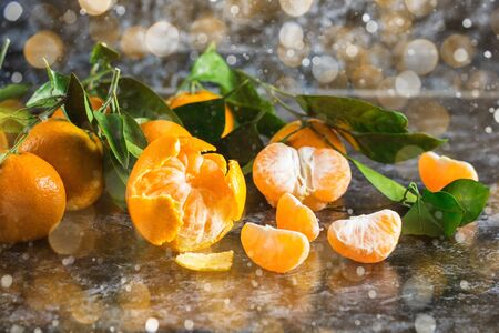 Many orange tangerines with green leaves on dark background. Peeled mandarin slices. Toned bokeh and snow Stock fotó