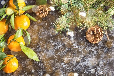 Many Christmas orange tangerines with green leaves and fir tree on dark background with copy space. Toned bokeh and snow Stockfoto