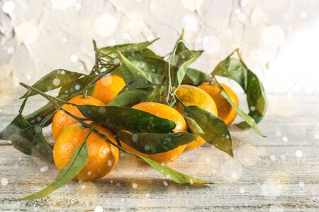 many orange tangerines with green leaves on white wooden background. Toned bokeh and snow