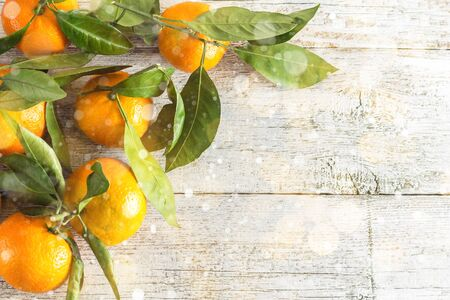 Border of Many orange tangerines with green leaves on white wooden background. Top view and copy space. Toned bokeh and snow