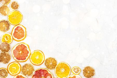 Border of Dried slices of various citrus fruits on white background. Many Orange lemon grapefruit with copyspace. Toned bokeh and snow Stock fotó
