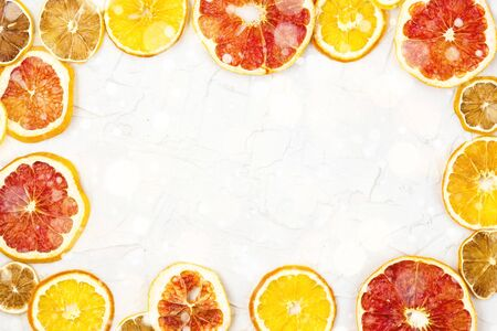 Border of Dried slices of various citrus fruits on white background. Many Orange lemon grapefruit with copyspace. Toned bokeh and snow Stockfoto
