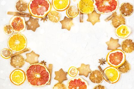Border of Dried slices of various citrus fruits gingerbread and spices on white background with copyspace. Christmas frame. Toned bokeh and snow Stock fotó