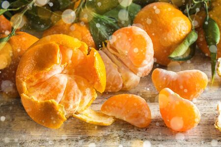 Many orange tangerines with green leaves on white wooden background. Peeled mandarin slices. Toned bokeh and snow Stock fotó