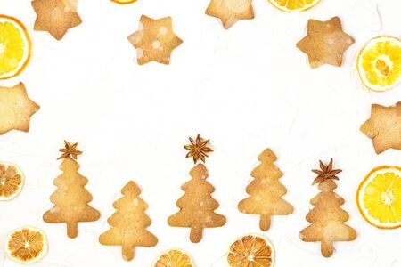 Five Christmas tree cookies with star toppers and dry orange on white background with copyspace. Toned bokeh and snow Stock fotó