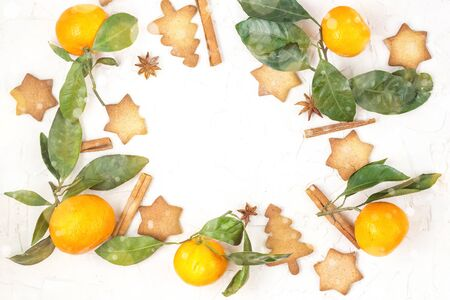 Border of Christmas star cookies with spices and mandarin on white background with copyspace. Top view. Toned bokeh and snow