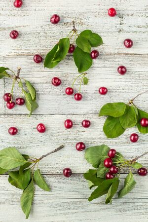 Red ripe cherry berries and green leaves on white wooden background. Flat lay, top view