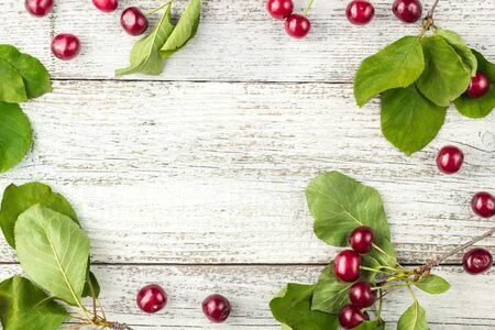 Frame of Red ripe cherry berries and green leaves on white wooden background. Flat lay, top view