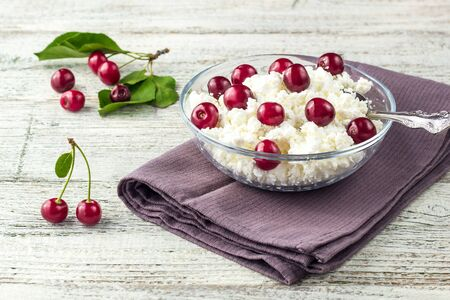 Breakfast from cottage cheese with cherry in transparent bowl on a white wooden background Фото со стока