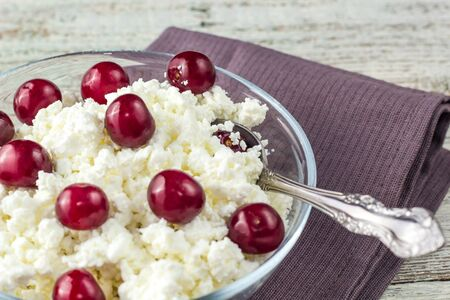 Breakfast from cottage cheese with cherry in transparent bowl on a white wooden background Stockfoto
