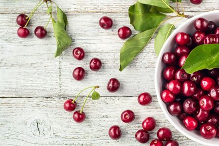 Fresh sweet cherries bowl with leaves in water drops on white wooden background, top view Stockfoto
