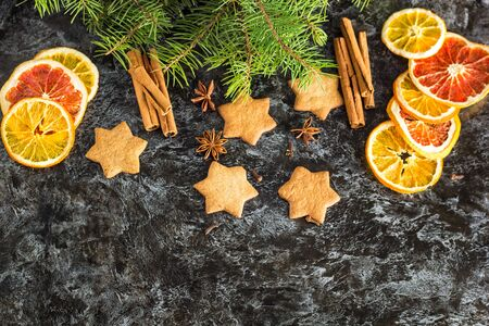 Christmas background with fir tree dry orange cinnamon anise and star of Gingerbread cookies on dark background with copyspace