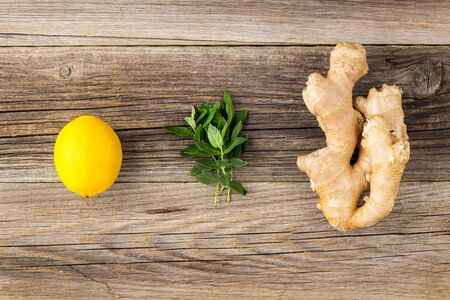 fresh ginger lemon and mint on wooden background. Copy space