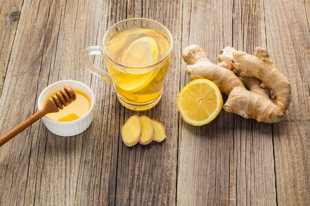 Ginger tea with lemon and honey on a wooden background. Hot healthy winter drink with copy space