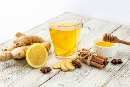 Autumn hot drink tea with ginger, lemon, honey and spices on white wooden background. Copy space