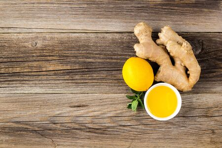 Ginger root lemon mint and honey ingredients for natural hot drink on wooden background. copy space