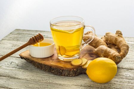 Ginger tea with lemon and honey on a white wooden background. Hot healthy winter drink with copy space