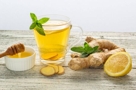 Ginger tea with lemon mint and honey on a white wooden background. Hot healthy winter drink with copy space