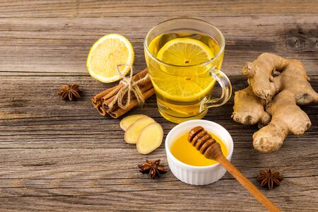 Autumn hot drink tea with ginger, lemon, honey and spices on wooden background. Copy space