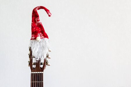 acoustic guitar with red Santa hat. Christmas song music concept on white background with copyspace