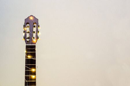 acoustic guitar wrapped in a luminous garland. Christmas gift with space for text