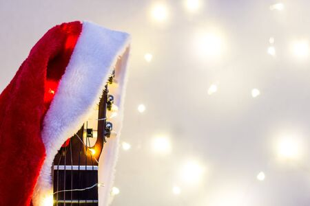 Acoustic Guitar with red Santa hat and light garland. Christmas music song concept with copyspace on white background