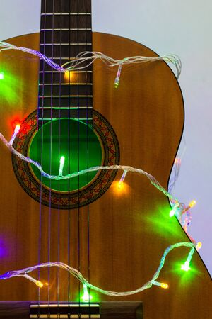 Acoustic guitar wrapped by colorful garland. christmas and new year music gift as background