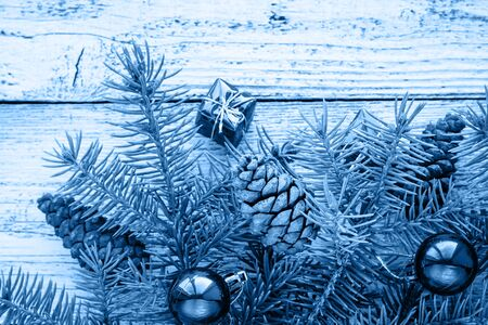 Christmas accessories in blue, cone and fir branches on wooden white background in classic blue trendy color. Color of the year 2020. Imagens