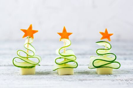 Creative concept set christmas trees of cucumber, cheese and star of carrot. Funny kids food for new year party on grey background with copy space
