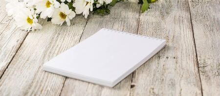 spring bouquet of white daisies with clean notebook to write on white wooden table. Copy space