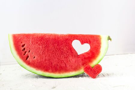 Fresh juicy watermelon slice with heart shape hole on white background. Valentines, love, summer concept with copy space