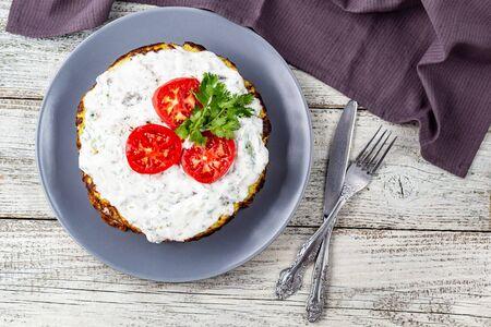 Zucchini-Kuchen mit Tomaten und frischer Petersilie auf weißem Hintergrund aus Holz. Draufsicht mit Serviettengabel und Messer