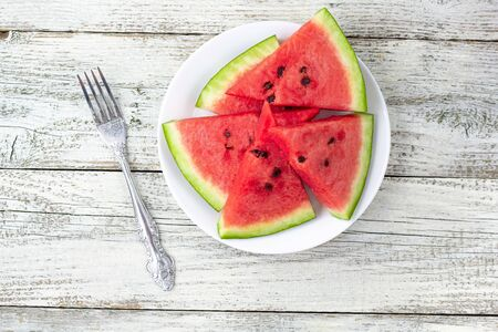 Ripe watermelon slices on plate with a fork on white wooden background