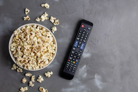 A white bowl of popcorn and TV remote on a grey background. The concept of watching TV, film, TV series, sports, shows.